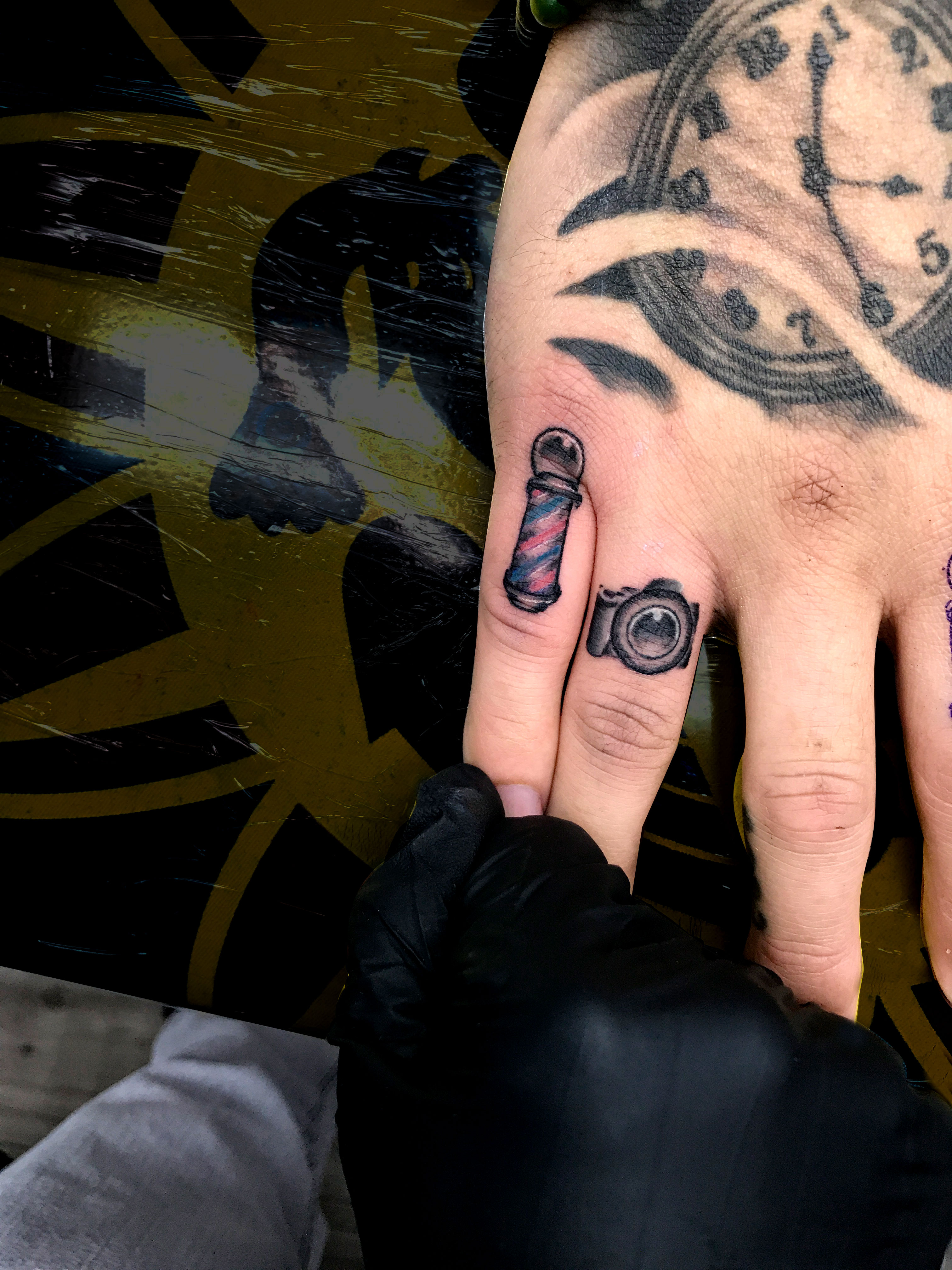 Q Tattoo in Huntington Beach - Sara Delara - small finger tattoos - camera and barber shop