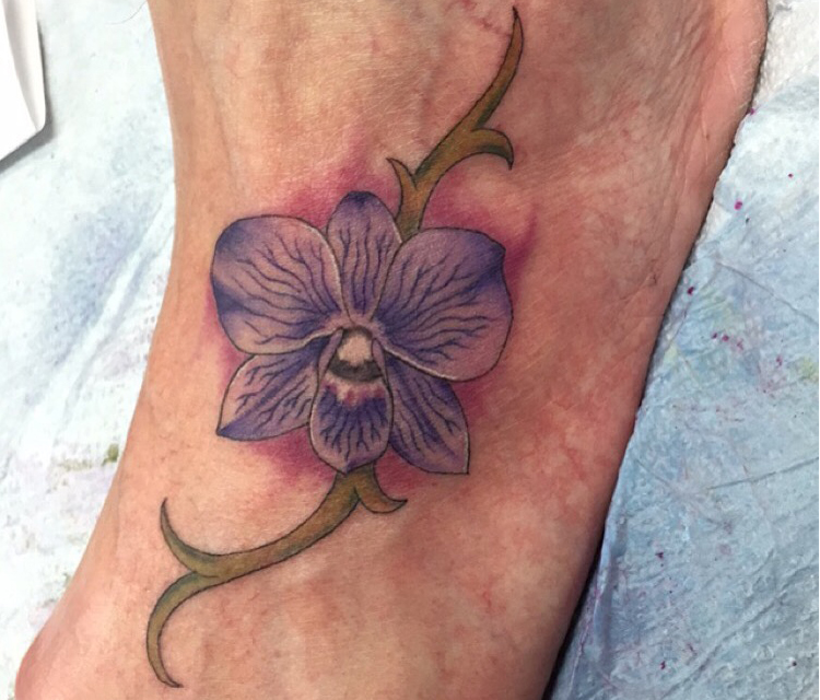 Q Tattoo in Huntington Beach - Sara Delara - purple flower on foot